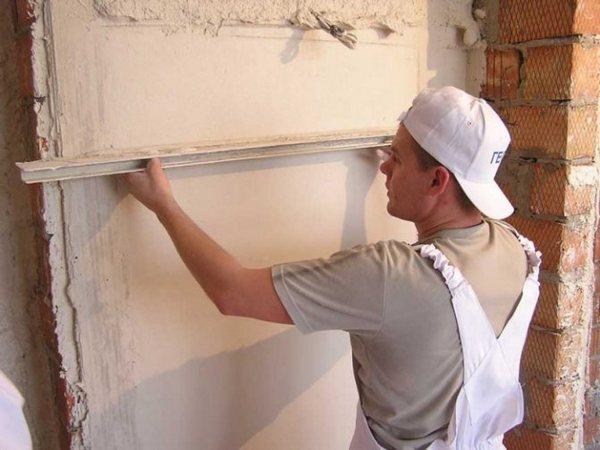 Процесс разравнивания раствора при оштукатуривании стен